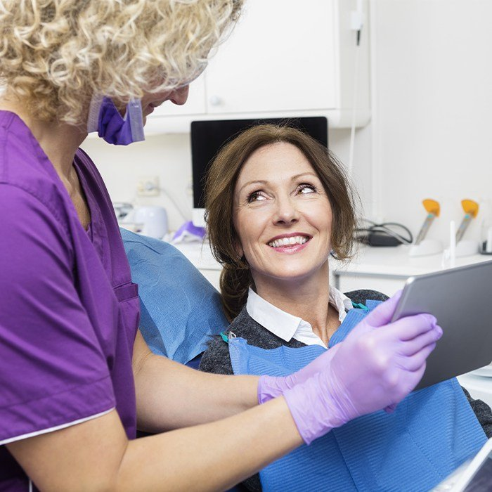 woman smiling up at dental assistant