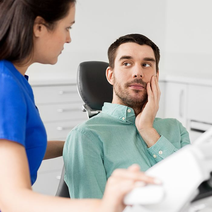 man in green shirt with dental emergency
