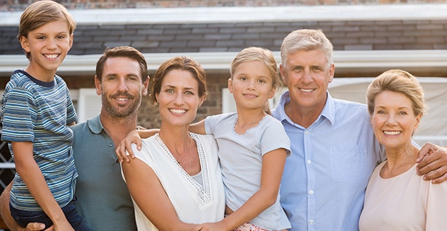 family of 6 smiling outside of house