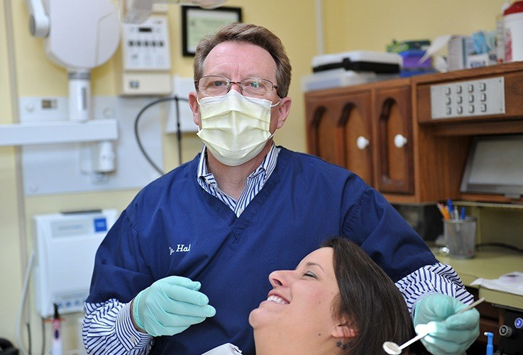 Dr. Lippard with facemask on by patient in exam chair