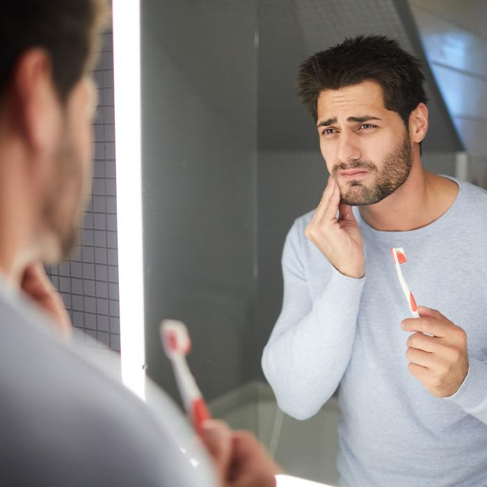 man holding toothbrush and jaw in pain