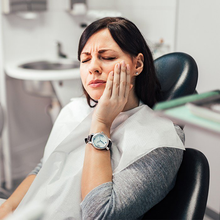 woman wearing watch wincing in pain and holding jaw