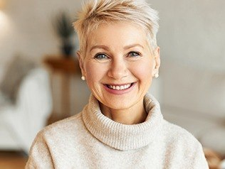 woman wearing tan sweater smiling at camera