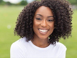 woman in white with curly hair smiling