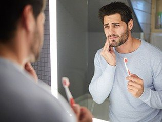man holding toothbrush and cheek in pain