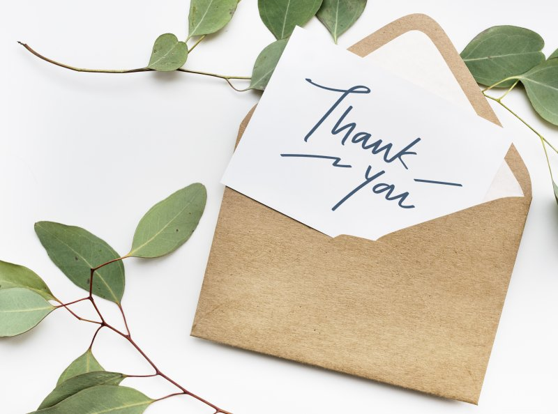 Thank you card and envelope on table with greenery